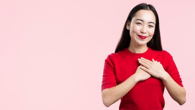 Copia-spazio donna con labbra rosse con la mano sul cuore Foto Gratuite