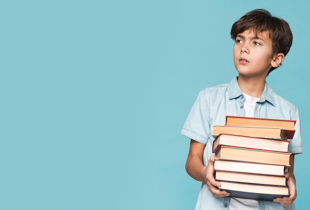 Copy-space young boy holding books Free Photo