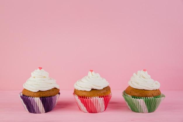 Copyspaceと誕生日のための3つのカップケーキ 無料写真