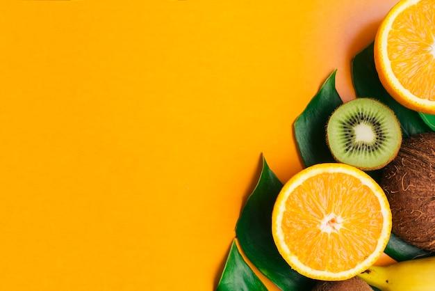 Тропические фрукты фон с copyspace с фруктами на листьях и copyspace Бесплатные Фотографии