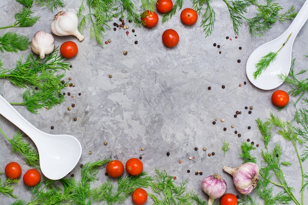 Copyspace frame of cherry, dill, pepper spice, garlic and ladles on a gray background. top view Premium Photo