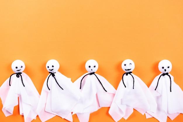 ハロウィーンの工芸品、copyspaceとオレンジ色の紙の背景に紙の幽霊のトップビュー Premium写真