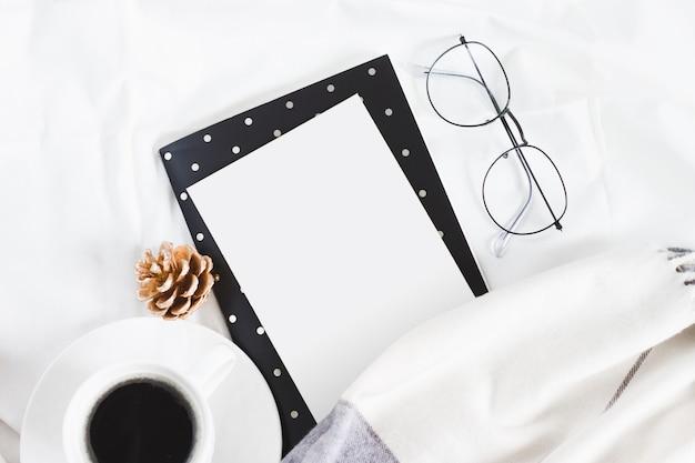 ベッド、眼鏡、スカーフ、白いコーヒーカップに白い紙。 copyspaceで冬フラットレイアウト Premium写真