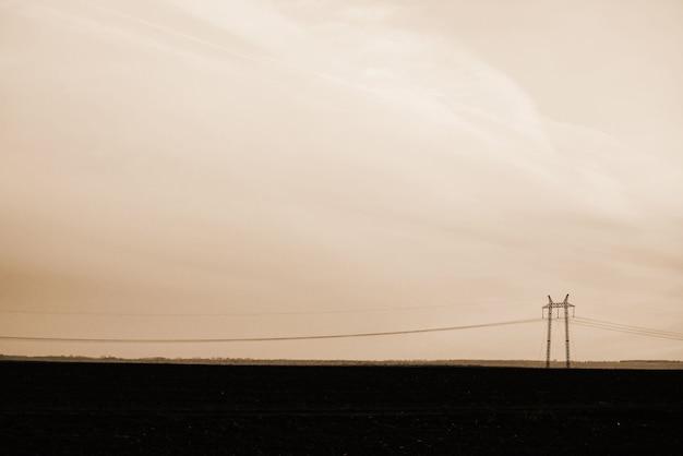 空のクローズアップの背景の電力線。セピア色のトーンでcopyspaceと電柱のシルエット。地上の高電圧のワイヤ。モノクロの電気産業。 Premium写真