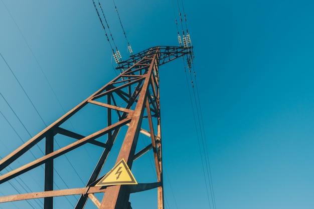 青空のクローズアップの背景の電力線。ポールの電気ハブ。 copyspaceの電気機器。空に高電圧のワイヤ。電気産業。雷の警告サインとタワー。 Premium写真