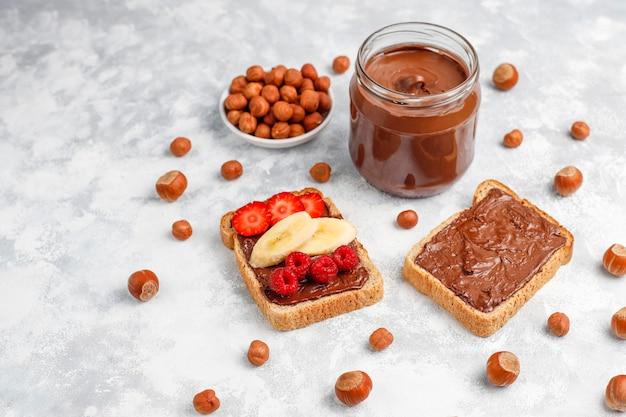 コンクリート、copyspaceのガラスの瓶にヘーゼルナッツとチョコレートスプレッドまたはヌガークリーム 無料写真
