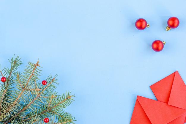 Китайский новый год и лунный новый год. ветки еловые, красные конверты с карманными деньгами. елочные украшения, специи на синем. плоское положение, вид сверху, copyspace Premium Фотографии