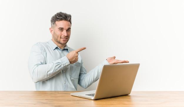Молодой красавец, работающих с его ноутбук возбужденных, держа copyspace ладони. Premium Фотографии
