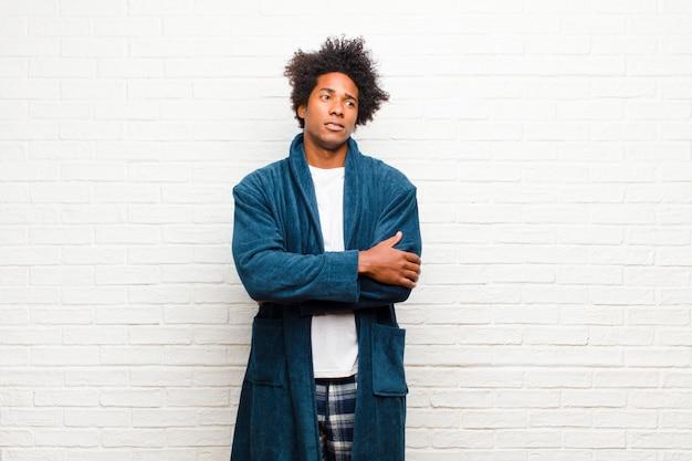 若い黒人男性のパジャマを着て疑問や思考、唇をかむと不安と緊張を感じて、レンガに対して側のcopyspaceを探して Premium写真