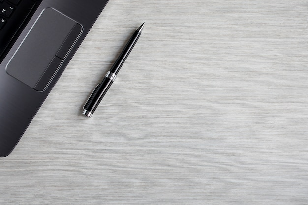 ノートパソコンとペンと白いオフィステーブル。 copyspaceとトップビューの背景。テーブルのワークスペース。仕事とオフィスのコンセプト Premium写真