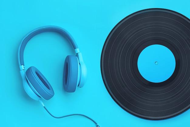 色付きの背景にビニールレコードとターコイズブルーのヘッドフォン。 copyspaceの音楽コンセプト。分離されたシアンの背景にヘッドフォン Premium写真