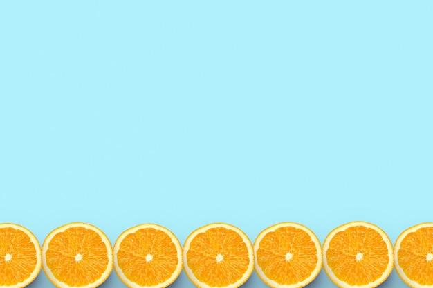 Красочные фрукты граница свежих апельсиновых дольок на цветном фоне с copyspace Premium Фотографии
