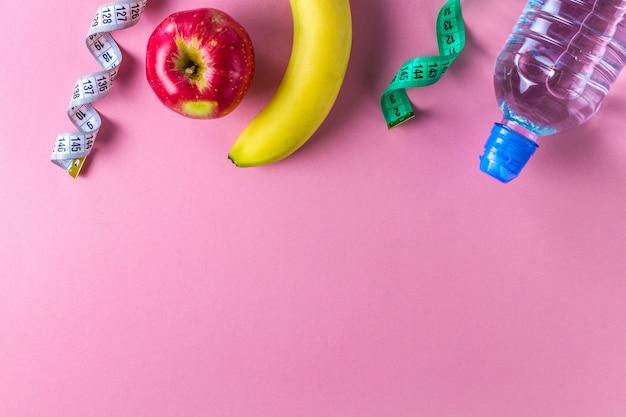 Бутылка воды, яблоко, банан и рулетка. спорт и диетическое понятие. спорт и здоровый образ жизни. copyspace фон Premium Фотографии