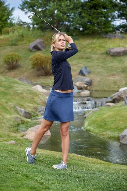 目標、copyspace。グリーンフィールドでゴルフ用品を保持している女性のゴルフ時間。卓越性、個人の職人技、ロイヤルスポーツ、スポーツバナーの追求。 Premium写真