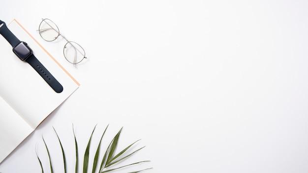 デスクトップフラットレイアウト。白い背景の上のメモ帳、時計、メガネ、手のひら。 copyspace。 Premium写真