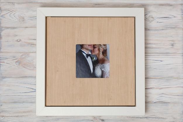 フォトブック用のスタイリッシュなボックス。家族のフォトアルバム用の段ボール箱。 copyspaceの結婚式のフォトアルバム付きのボックス。箱に入った革の結婚式の写真集。 Premium写真