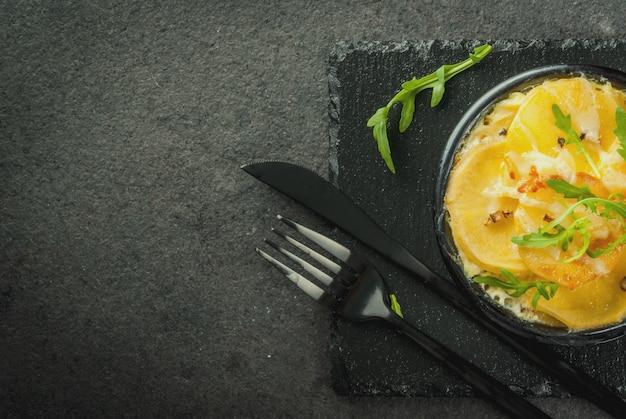 Запеканка. французская кухня. домашний картофельный гратен в миску для выпечки. на черном каменном фоне. с листьями свежей рукколы для украшения. вид сверху copyspace Premium Фотографии
