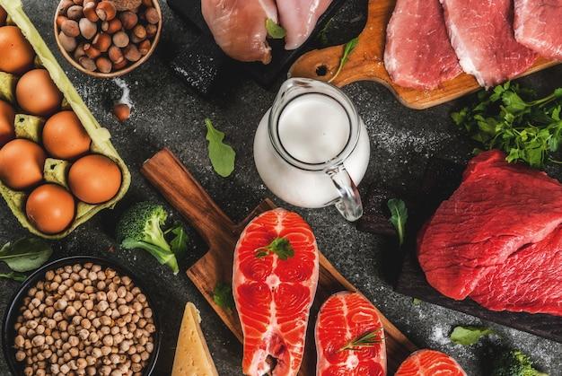 Здоровая пища фон. выбор источников белка: говядина и свинина, куриное филе, лосось, яйцо, фасоль, орехи, молоко. вид сверху copyspace, темный фон Premium Фотографии