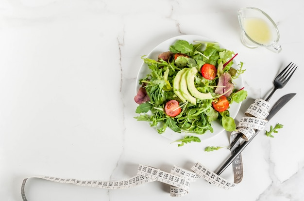 Концепция здорового сбалансированного питания, потеря веса, подсчет калорий. тарелка с листьями зеленого салата, помидорами, авокадо с заправкой из йогурта, белый стол, с вилкой, ножом, рулеткой, вид сверху copyspace Premium Фотографии