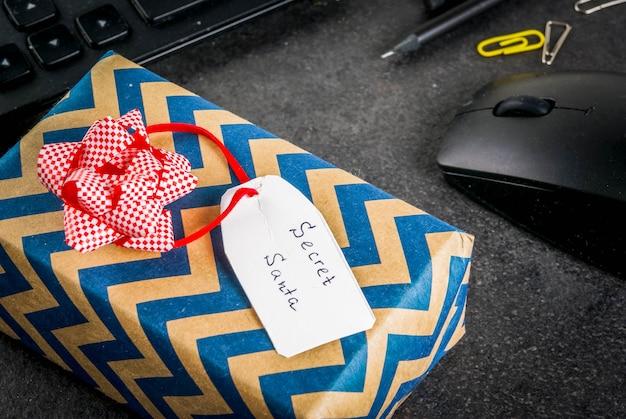 Празднование рождества в офисе, идея обмена дарами секрета санта. клавиатура, мышка, блокнот, ручки, карандаши, рождественский подарок. черный офисный стол, copyspace Premium Фотографии