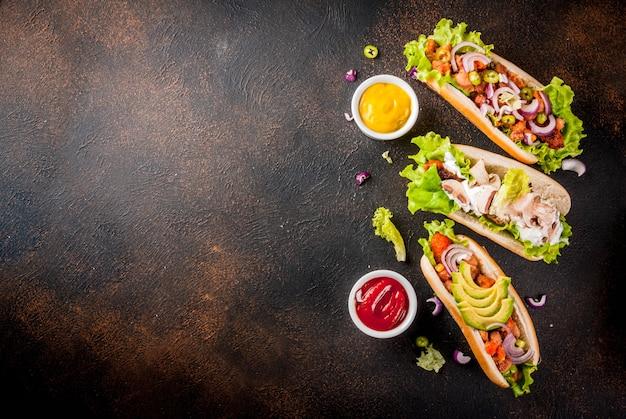 さまざまな自家製ビーガンキャロットホットドッグの品揃え、揚げ玉ねぎ、アボカド、唐辛子、マッシュルーム、トマト、豆、暗いさびたcopyspaceトップビュー Premium写真