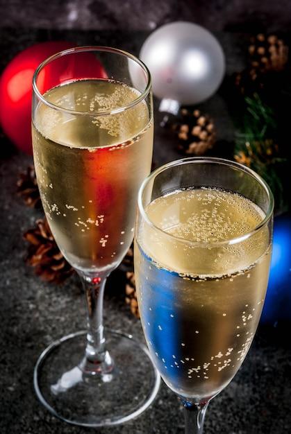 メガネ、クリスマスのカラフルなボール、松ぼっくり、暗い石、セレクティブフォーカスcopyspaceの新年静物組成のシャンパンを乾燥します。 Premium写真