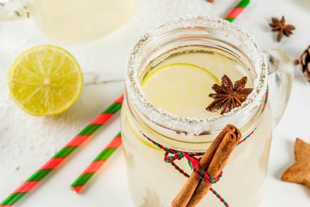 秋と冬の飲み物。クリスマスの休日の飲み物。ライムジュース、シナモン、リキュール、砂糖、アニスの星が付いたお祝いスノーボールカクテル。クリスマスの装飾、copyspaceと白いテーブルの上 Premium写真