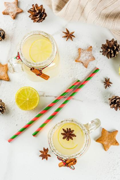秋と冬の飲み物。クリスマスの休日の飲み物。ライムジュース、シナモン、リキュール、砂糖、アニスの星が付いたお祝いスノーボールカクテル。クリスマスの装飾、copyspaceトップビューで白いテーブルの上 Premium写真