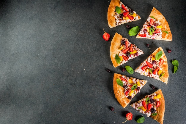 夏のおやつ。パーティーの食べ物。フルーツピザ、クリーム、スグリ、ヨーグルト、イチゴ、マンゴー、桃、バナナ、ブラックベリー、チョコレート、クルミ、ミント。黒いテーブルの上。 copyspaceトップビュー Premium写真