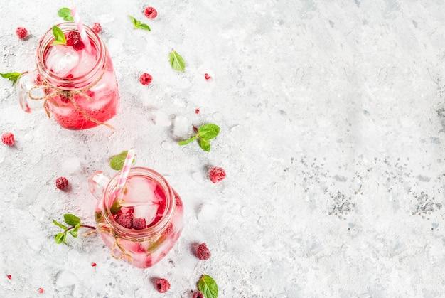 冷たい夏の飲み物、ラズベリーサングリア、レモネードまたはモヒート、新鮮なラズベリーとシロップ、ミントの葉、灰色の石copyspaceトップビュー Premium写真