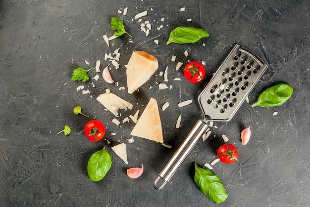 イタリア料理の材料。すりおろしたパルメザンチーズと、暗いコンクリートのテーブルに、おろし金、バジルの葉、ニンニク、チェリートマトを添えた作品。トップビューcopyspace Premium写真