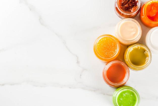 さまざまな自家製ベビー野菜や果物のピューレ、白い大理石のcopyspaceトップビュー Premium写真