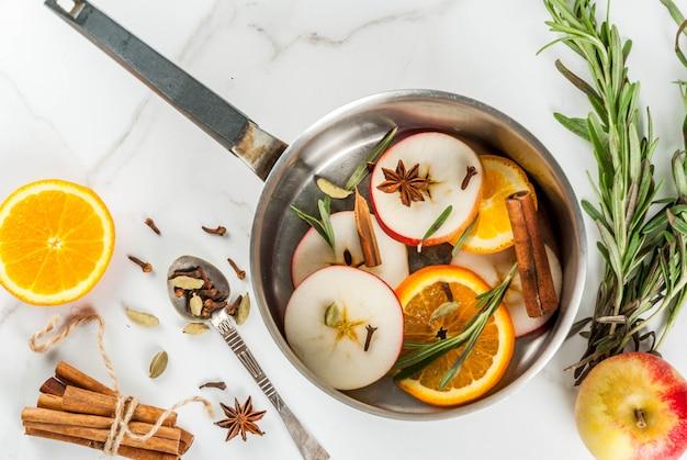 伝統的な冬とクリスマスの飲み物、柑橘類、リンゴ、白い大理石のテーブルの上のアルミのキャセロールのスパイスとホットワインの材料。 copyspaceトップビュー Premium写真