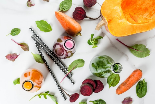 ビーガンダイエット食品。カラフルな新鮮な有機スムージーの選択は、秋野菜と一緒に飲みます:ビートルート、カボチャ、ニンジン、葉物野菜。ボトル、白いテーブル。 copyspaceトップビュー Premium写真