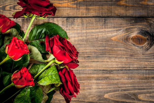 休日、バレンタインデー。赤いバラの花束、赤いリボンとネクタイ。木製のテーブル、トップビューcopyspace Premium写真