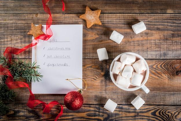 クリスマス、新年のコンセプト。木製テーブル、リストを行うためのノート、ジンジャーブレッド、ギフト、ホットチョコレート、クリスマスツリー、ココアマグカップ、クリスマスボール、松の木、赤いリボン、マシュマロ。トップビューcopyspace Premium写真