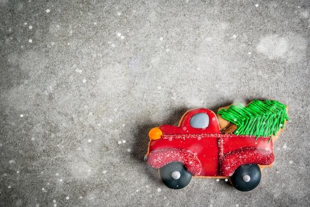 灰色の石のテーブルの上にクリスマスツリーが付いている車の形でクリスマスの手作りのカラフルなジンジャーブレッドクッキー。トップビュー、copyspace Premium写真