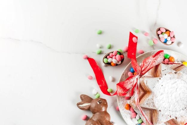 伝統的なイタリアのフルーツケーキパネトーネパンドーロ、お祝いの赤いリボン、イースターのウサギ、甘いお菓子の卵の装飾、木製の家、copyspaceトップビュー Premium写真