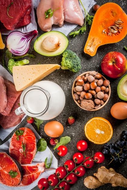 Здоровая диета . органические пищевые ингредиенты, суперпродукты: говядина и свинина, куриное филе, лосось, фасоль, орехи, молоко, яйца, фрукты, овощи. стол из черного камня, вид сверху copyspace Premium Фотографии