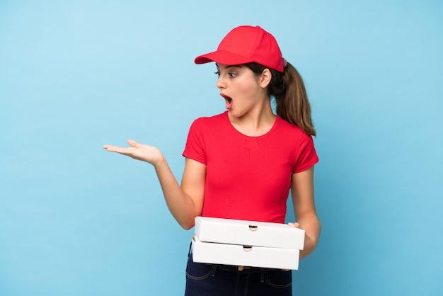手のひらに想像上のcopyspaceを保持しているピザの壁を保持している若い女性 Premium写真