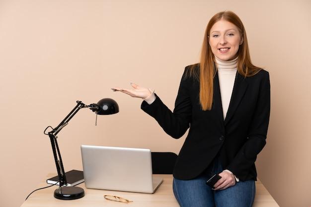Деловая женщина в офисе, держа copyspace мнимой на ладони Premium Фотографии