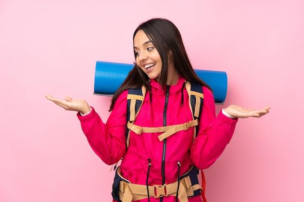 Молодая женщина альпиниста с большой рюкзак, держа copyspace двумя руками Premium Фотографии