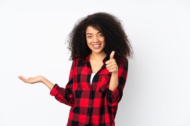 Молодая афро-американская женщина над изолированной стеной держа copyspace мнимое на ладони для того чтобы вставить объявление и с большими пальцами руки вверх Premium Фотографии