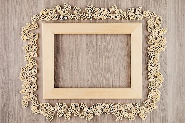 装飾的なフレームの背景として空copyspaceとベージュ茶色の木の板にイタリアの乾燥海パスタ Premium写真