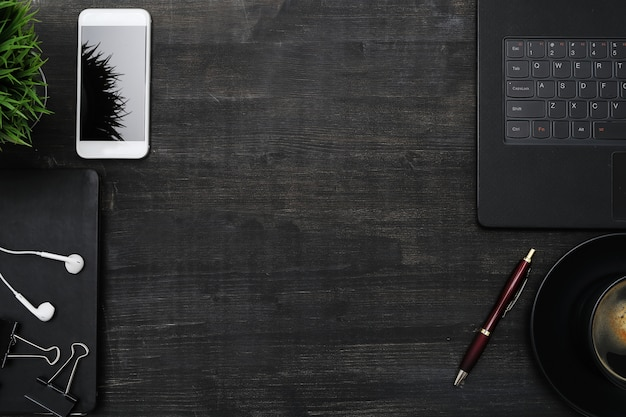スマートフォン、ラップトップ、黒いテーブルのある職場。トップビューcopyspace背景 無料写真