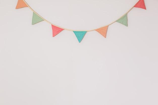 Гирлянда милые флаги партии висит на стене. фон с copyspace, символизирующий домашний праздник, день рождения или праздничное настроение Premium Фотографии