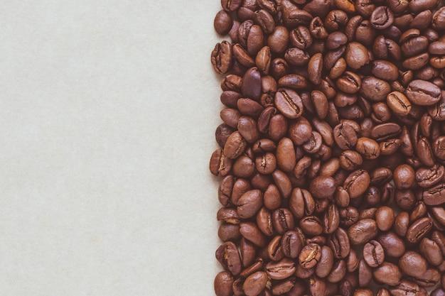 Черные кофейные зерна на бумажной предпосылке с copyspace. Premium Фотографии