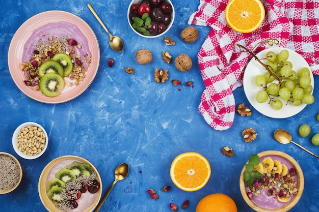 ベリーの植物ベースのヨーグルトボウルのグラノーラ、チア種子、様々な果物、copyspaceと青の背景にナッツの健康的なビーガン朝食とフラットレイ Premium写真