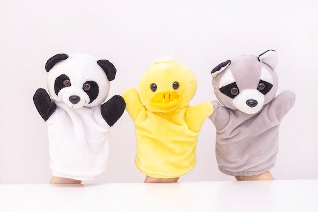 Кукольный театр на белом фоне. дружелюбные животные держатся за руки. концепция игры с детьми, дружба, семья, развлечения. няня развлекает детей. copyspace Premium Фотографии