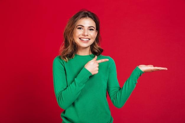 幸せな若いきれいな女性を示すcopyspaceポインティング。 無料写真